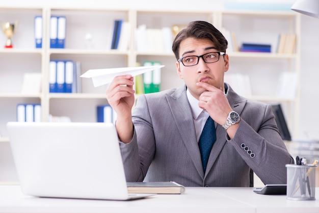 Zakenman met papieren vliegtuigje in kantoor