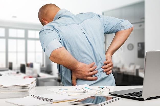 Zakenman met rugpijn een kantoor. pijnbestrijding concept