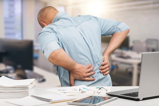 Zakenman met rugpijn zonde een kantoor. pijnbestrijding concept