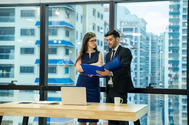 Zakenman met secretaresse werken en communiceren terwijl in een modern kantoor, man en vrouw bespreken samenwerken.