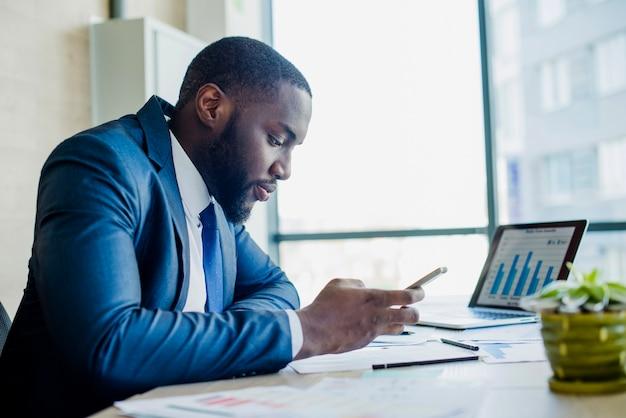 Zakenman met smartphone in zijn kantoor