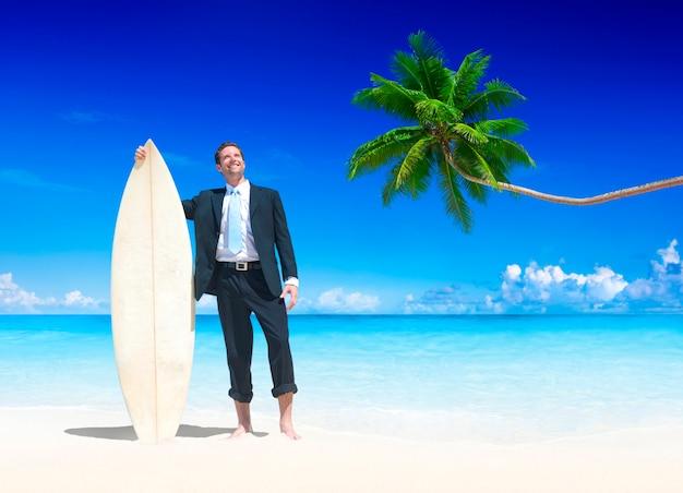 Zakenman met surfplank op het strand.