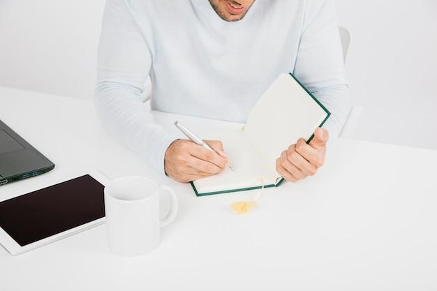 Zakenman met tablet schrijven op zijn dagboek