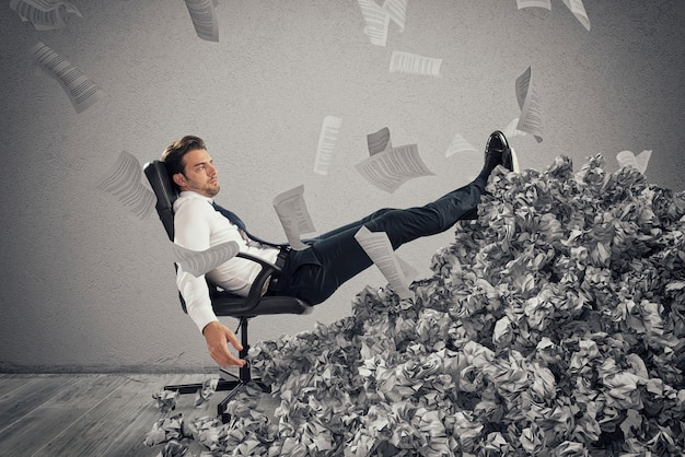 Zakenman met vel papier overal in kantoor. begraven door bureaucratie. concept van overwerk