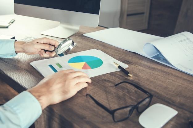 Zakenman met vergrootglas en financiële grafiek in kantoor
