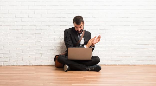 Zakenman met zijn laptop zittend op de vloer applaudisseren na de presentatie in een conferentie