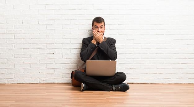Zakenman met zijn laptop zittend op de vloer die de mond met beide handen