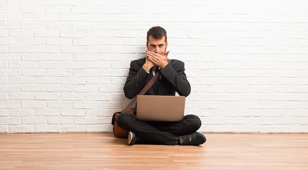 Zakenman met zijn laptop zittend op de vloer die mond behandelt met handen voor iets ongepast zeggen