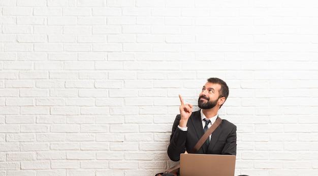 Zakenman met zijn laptop zittend op de vloer een groot idee te wijzen en omhoog te kijken