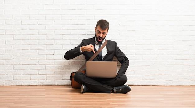 Zakenman met zijn laptop zittend op de vloer gefrustreerd door een slechte situatie en wijst naar de voorkant