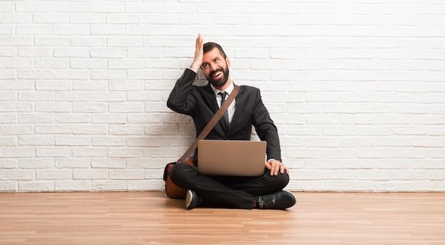 Zakenman met zijn laptop zittend op de vloer heeft net iets gerealiseerd en is van plan de oplossing