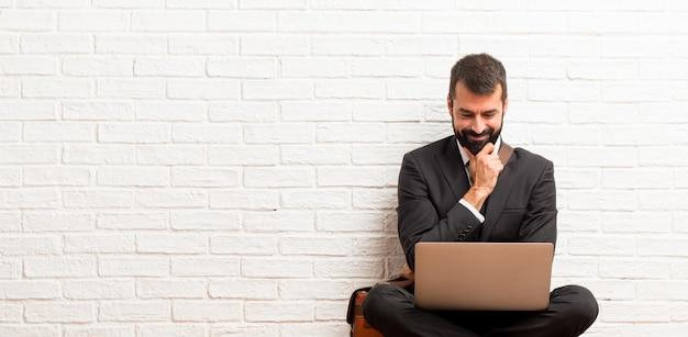 Zakenman met zijn laptop zittend op de vloer lacht en kijkt naar de voorkant met vertrouwen gezicht