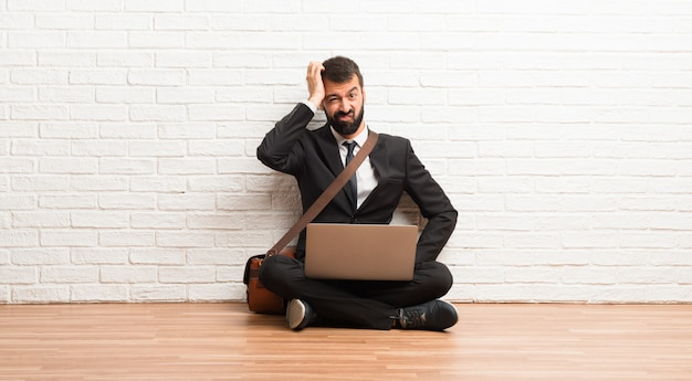 Zakenman met zijn laptop zittend op de vloer met een uitdrukking van frustratie en niet begrijpen