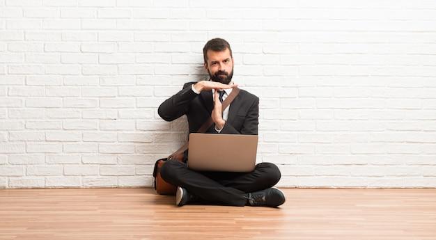 Zakenman met zijn laptop zittend op de vloer stop gebaar maken met haar hand om een daad te stoppen