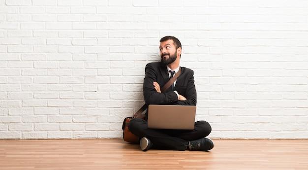 Zakenman met zijn laptop zittend op de vloer twijfels gebaar maken terwijl het opheffen van de schouders