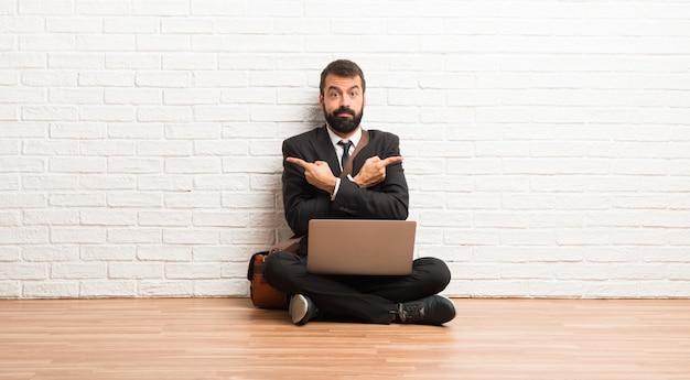 Zakenman met zijn laptop zittend op de vloer wijzend naar de zijtakken met twijfels