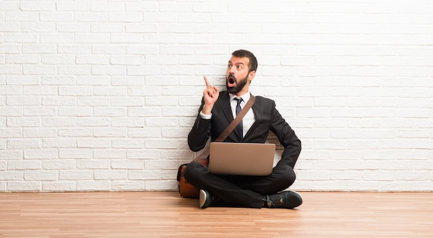 Zakenman met zijn laptop zitting op de vloer die en een idee bevinden zich denken die de vinger benadrukken