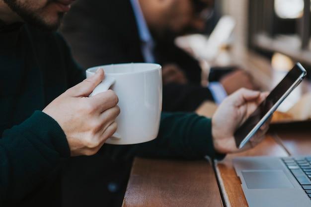 Zakenman met zijn telefoon in een café