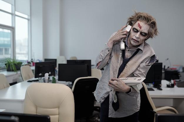 Zakenman met zombie make-up die aan de telefoon spreekt in een kantooromgeving