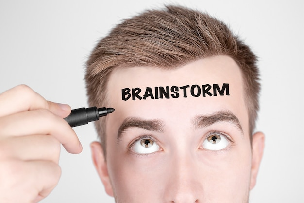 Zakenman met zwarte stift schrijft het woord brainstorm op zijn voorhoofd