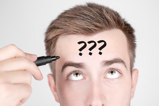 Zakenman met zwarte stift schrijft het woord vragen op zijn voorhoofd