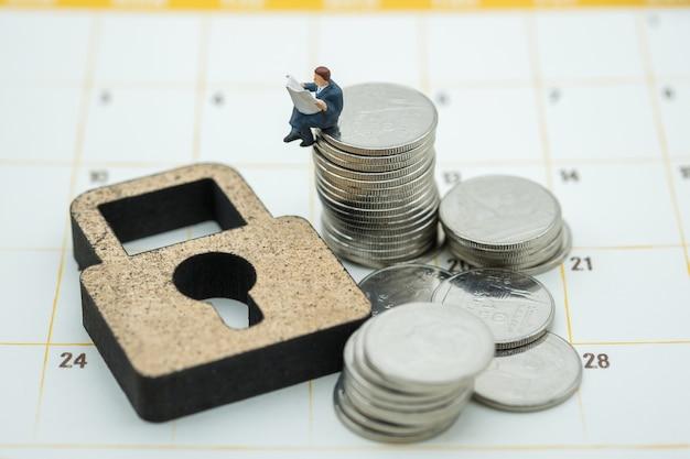 Zakenman miniatuur figuur lezing krant op stapel munten