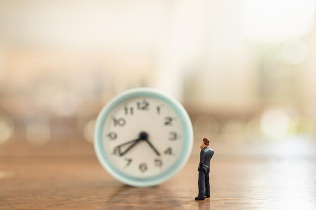 Zakenman miniatuur figuur mensen staan en kijken naar vintage ronde klok