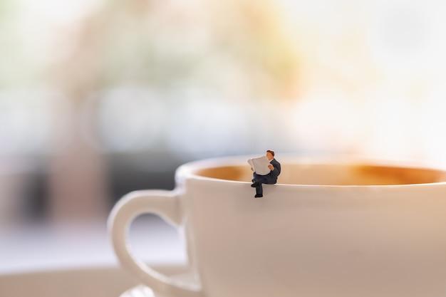 Zakenman miniatuur mini mensen cijfers zitten en lees een krant op de kop warme koffie.