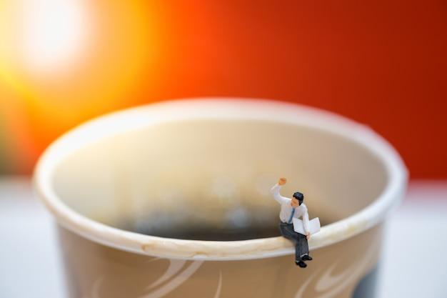 Zakenman miniatuurcijfers zitten en krantendocument kop hete zwarte koffie lezen.