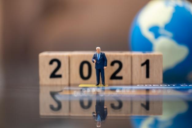 Zakenman miniatuurfiguur mensen staan op creditcard met houten nummer 2021 blok en mini wereldbal als achtergrond.