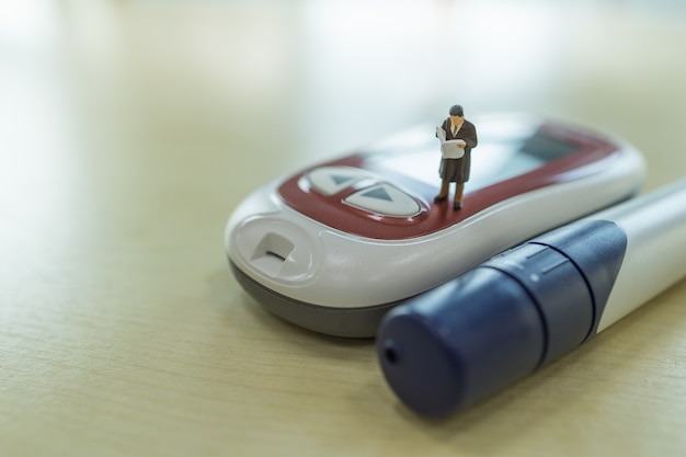 Zakenman miniatuurfiguur staan en lezen boek of krant op glucosemeter