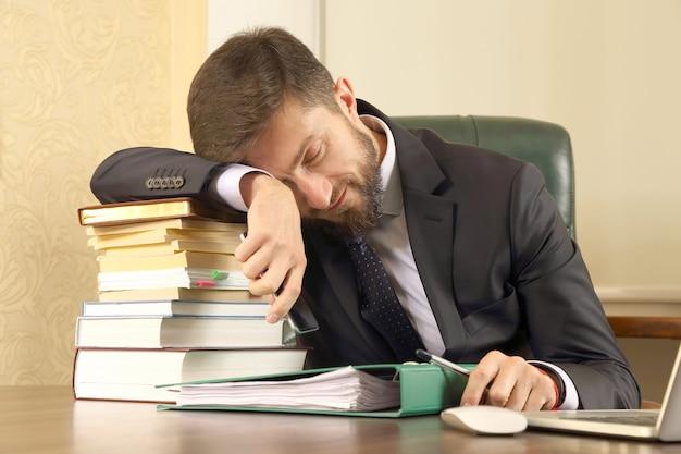 Zakenman moe van het werken met boeken en documenten