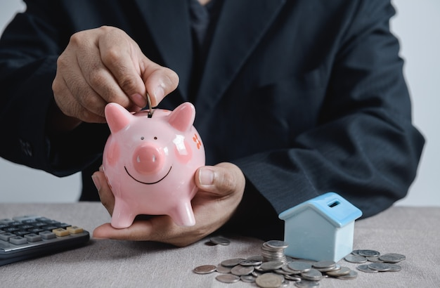 Zakenman munt aanbrengend het spaarvarken, sparen voor nieuw huisconcept