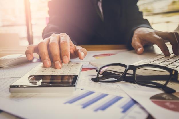 Zakenman of accountant die aan calculator werken om bedrijfsgegevensconcept te berekenen op kantoor.