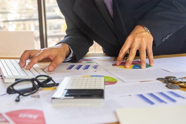 Zakenman of accountant die aan calculator werken om bedrijfsgegevensconcept te berekenen.