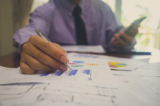 Zakenman of accountant die aan calculator werkt om bedrijfsgegevensconcept te berekenen.