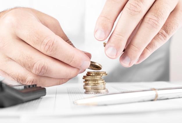 Zakenman of accountant die geld tellen en stapel coi maken