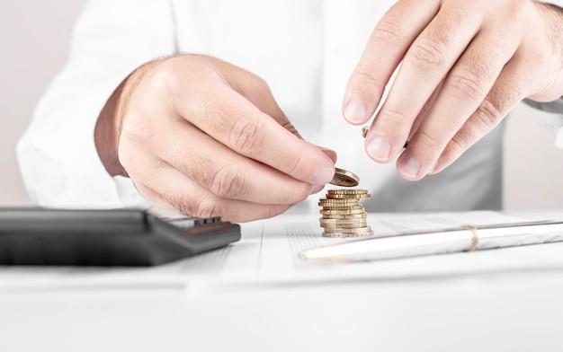 Zakenman of accountant die geld tellen en stapel muntstukken maken op financiële gegevens