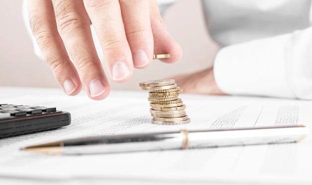 Zakenman of accountant die geld tellen en stapel muntstukken maken