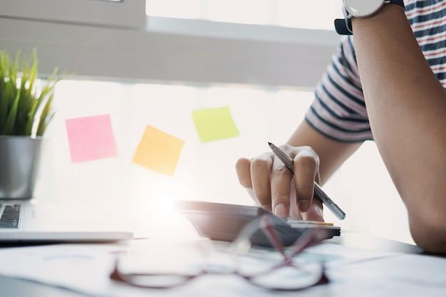 Zakenman of accountant hand met pen werkt op calculator om bedrijfsgegevens te berekenen