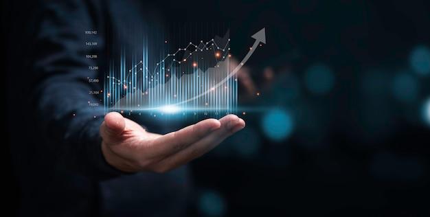 Zakenman of handelaar die gloeiende virtuele technische investeringsgrafiek toont voor analysebeurs, financieel bankwezen en schavend concept.