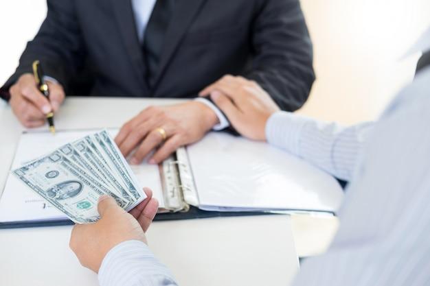 Zakenman of politicus die steekpenningen en handen schudden met geld in een kostuum, corruptie