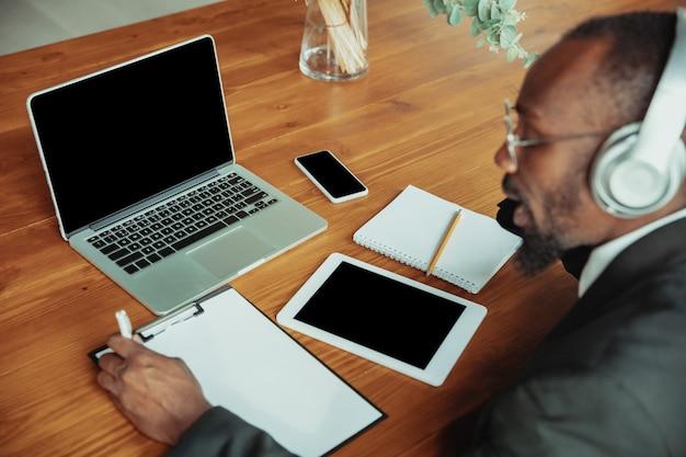 Zakenman of student die thuis werkt, wordt geïsoleerd of houdt quarantaine vanwege het coronavirus. afro-amerikaanse man met laptop, tablet en koptelefoon. online conferentie, les, kantoor op afstand.