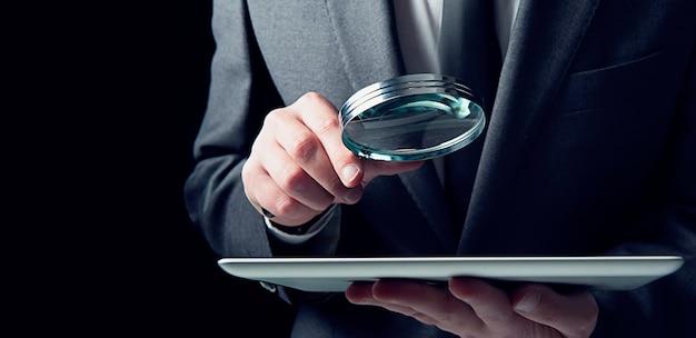 Zakenman onderzoekt een geïnfecteerde tablet met een vergrootglas. concept van internetbeveiliging