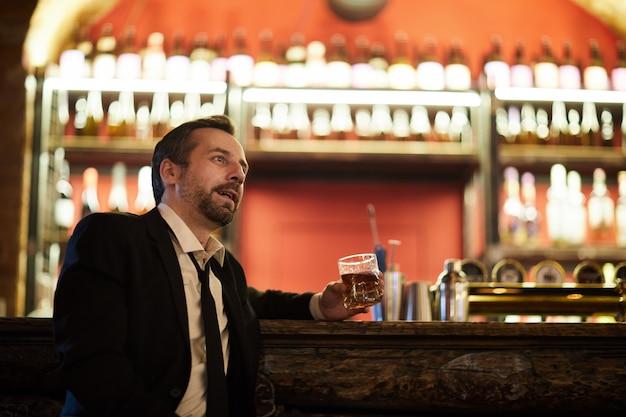 Zakenman ontspannen door bar counter