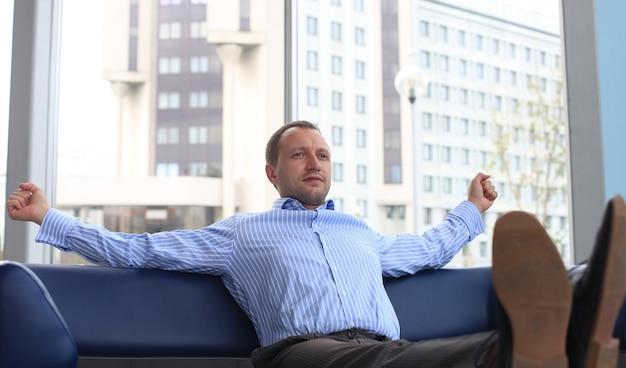 Zakenman ontspannen op kantoor met zijn schoenen op het bureau