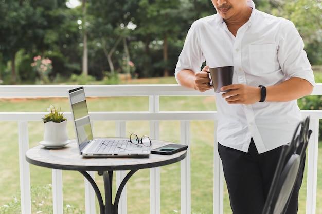 Zakenman ontspannen staande op terras hand met koffie met laptop op tafel.