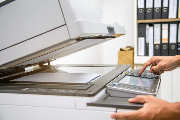Zakenman op de knop voor het gebruik van fotokopieerapparaat of printer op kantoor.