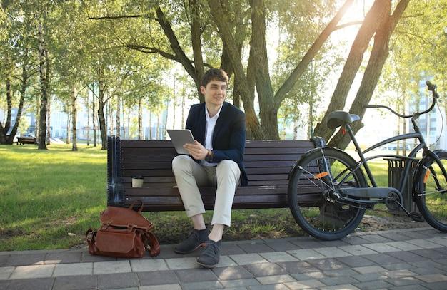 Zakenman op een koffiepauze. hij zit op een bankje en werkt aan touchpad, naast de fiets.
