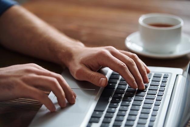 Zakenman op een van de knoppen van laptop toetsenbord te drukken tijdens het netwerken of het organiseren van werk door een bureau